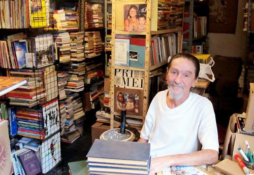 Cesinha em meio a milhares de livros espalhados por várias estantes em sua casa.