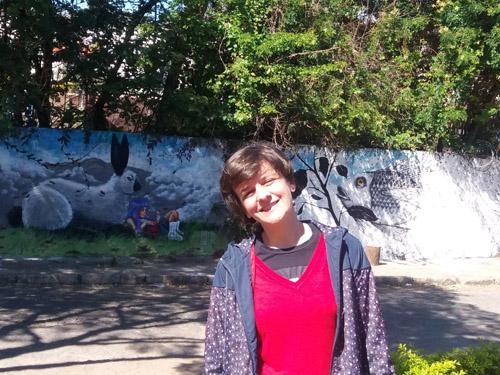 Gisele Milagres junto do muro do Metrô, coberto pela obra do TAU